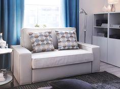 Un salón con un sofá de dos plazas con una funda beige junto a un mueble con puertas en blanco