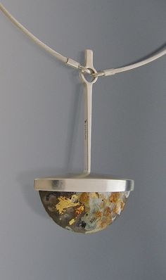 "Dots Pendant II by Tom McCarthy. Sterling, concrete, gold leaf, ink, rust, house paint. 2 3/8"" x 1 1/2"" x 5/8"". 2010"