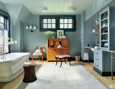 A Swedish Empire secretary and chair stand in the master bath of an Adirondacks, New York, home designed by Thom Filicia; the beadboard walls are painted in a blue-tinged Benjamin Moore gray (as are the Feiss ceiling fixtures), the sconces are from Circa Lighting, the tub is by Waterworks, and the Oly bench is upholstered in goat hide.