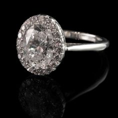 Beautiful 1.51ct oval brilliant diamond within a diamond surround and mounted as a ring in platinum Hancocks, London, contemporary