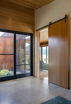 Polished concrete floors and barn door Wolf Creek View Cabin by Balance Associates Architects | HomeDSGN, a daily source for inspiration and fresh ideas on interior design and home decoration.