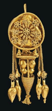 HELLENISTIC PERIOD, CIRCA LATE 4TH-3RD CENTURY B.C.   With pan-shaped disc, with stylized rosettes and palmettes radiating from central rosette, all with beaded wire borders, beneath four lengths of double loop-in-loop chain, in pairs, terminating either with an ivy-leaf or rosette below which hangs an amphora pendant, each pair flanking an inverted pyramidal pendant (one missing), with rosette masking the linking rings, the square top with pyramidal clusters of grains at each corner