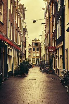 A sepia photograph of a street in Amsterdam, Netherlands. There are bicycles standing on the sides of the street. Travel photography.