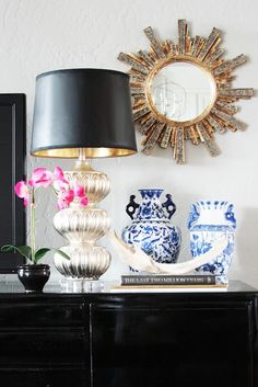 Chic vignette next to television on glossy black media cabinet. A mercury glass table lamp with black shade sits beside a small pink orchid, stacked books with antler on top and blue and white vases. The wall behind the vignette features a small gold sunburst mirror. The walls are Mindful Gray by Sherwin Williams.