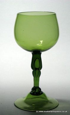 Georgian English Export Wine Glass c1750 Olive green it has a cup bowl above a complex hollow knopped stem and a high conical foot with snapped pontil.