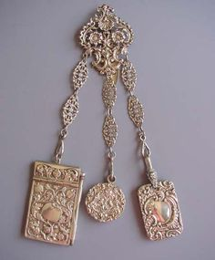 "VICTORIAN ornate silver chatelaine with pomegranate motif 1-3/4"" by 3"" notepad with paper and pencil, 1-1/3"" by 2"" dance pad with 3 leaves, griffin 1"" loop and 1-1/3"" round filigree vinaigrette on a 2-3/4"" top with 4"" ornate embossed and pierced flat link chains."
