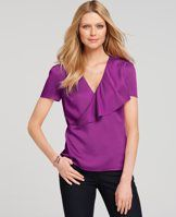 Asymmetrical Cascade Front Top - Cast in a rainbow of flattering hues, this sleek style sports an asymmetrical ruffle front for a delightful touch of feminine flair. V-neck with overwrap flounce and picot edge. Short sleeves with picot edge and cap pleats. Hidden back zipper.