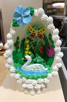 Royal icing swan transfer paddles regally amongst blossoms and a butterfly in this cut-away version of the classic panoramic sugar egg for Easter. Panoramic Sugar Easter Eggs, Sugar Eggs For Easter, Easter Bunny, Easter Cookies, Easter Treats, 3d Easter Cake, Easter Desserts, Candy Cane Crafts, Royal Icing Flowers