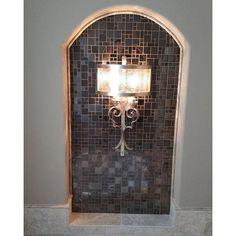 A beautiful sconce illuminates the Stainless Steel Vinton Metal Mosaic Tile