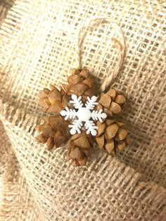 This adorable little wreath ornament is made from real, natural Hemlock pine cones featuring the snowflake style of your choice. It would make a great addition to your primitive holiday decorations. This ornament would also be perfect to top off any gifts! This mini pine cone