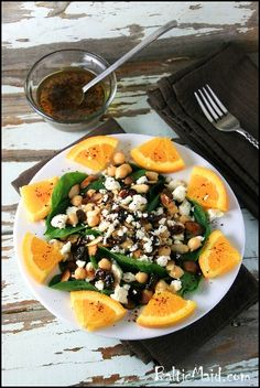 Arabic Spinach Salad  Ingredients    Dressing  3 tbsp fresh lemon juice  1 tbsp water  2 tsp liquid honey salt  1/2 tsp chili flakes, or to taste  2 generous pinches of cumin  5 tbsp olive oil  3 tbsp raisins    Salad  10.5 oz cooked garbanzo beans, or canned  5.3 oz young spinach  3.5 oz feta cheese 1 orange, sliced with peel, and then the slices are quartered  3 tbsp almond slices