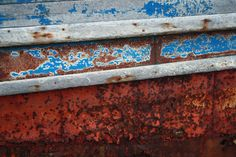 Old, rusty boat with blue paint coming off.