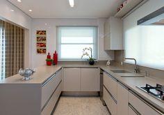 No ambiente da cozinha, a despensa foi transformada em área de serviço. Desse modo, o espaço foi ampliado. Para os móveis, foi utilizado MDF linho e tampos em Corian.