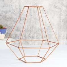 A stunning lampshade, made from copper toned iron wire bent into a vintage lampshade shape.Choose from tulip shape, parisol shape, or geometric shape.The perfect centre piece for any room needing a stylish vintage touch! These lampshades, made from copper toned iron wire, are incredibly on-trend with their shining copper colour. The perfect lighting accessory for when you want to amp up an open hanging bulb. We are happy to announce that we have won the not on the high street award for best…
