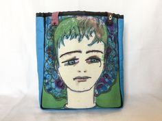 """Bobby - Blue Boy This bag measures 14"""" wide by 16"""" high by 6"""" deep The image is hand painted and dyed on linen The sides and back are a bright blue The inside is lined with a rich, soft tapestry like fabric 7"""" x 9"""" inside open side pocket 9"""" multi-colored woven straps All seams finished with pretty black ribbon"""