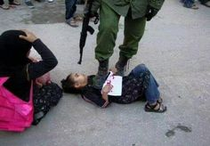 Israeli soldier holds little girl down with his foot - on her way to school - and points a gun at her face. #humanityLost