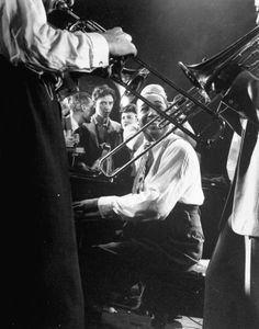 Composer-pianist-arranger Duke Ellington playing piano amidst two trombonists during an after-hours jam session with some of the most exciting jazzmen in the city at the studio of photographer Gjon Mili, 1943