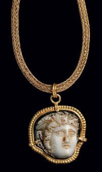 A Roman Onyx Cameo | c. 2nd century AD. | Carved in two layers, white on blue-gray, with a head of Medusa depicted turned slightly to her left, snakes radiating from her thick curly hair, one wing visible, the face well defined with the eyes articulated; mounted as a pendant in a modern gold setting, suspended from an ancient-style gold chain