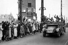 Dutch residents of Amsterdam welcome German soldiers on a Krupp Protze Kfz.69 artillery tractor, 1940