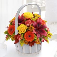 This chic basket arrangement reminds us of a warm bonfire with its array of yellow, red and orange shades.
