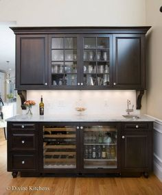 Wet bar with dark, raised-panel cabinetry, crown molding, corbels, wine  beverage fridge, and white stone countertop