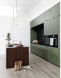 Grüne großflächige Küchenwand mit dunkler Kochinsel aus Holz, Küche mit viel Stauraum, moderne Küche mit Kochinsel, Kontrastreiche Küche, Küche mit Farbe, Ideen Küche