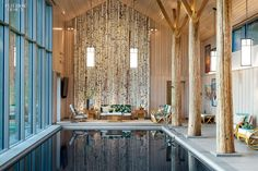 A Secret Pool House by BarlisWedlick Architects | White birch logs line an end wall.