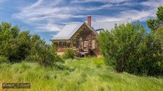 An pioneer school rests peacefully in knee high grass in the abandoned ghost town of Nemiskam Alberta.
