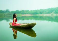 Chica navegando en su balsa de madera por el lago de aguas tranquilas
