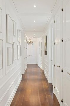 White hallway accented with ornate wall trim moldings is lined with gray framed gallery art.