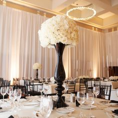 A tall black vase with white blooms creates a dramatic and chic centerpiece at @Mandy Dewey Seasons Hotel St. Louis