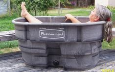 """Poor Woman's Hot Tub"" uses 100-gal. fiberglass livestock watering tank with a drain plub and hot water supply with a washing machine Y. Add Epsom salts and water the yard. Maggie Plummer in her soaking tub."