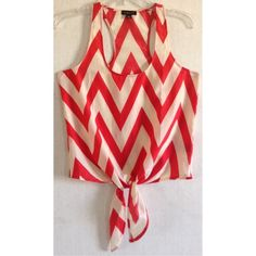 Timing Chevron Tie Front Tank Top Good condition! Some loose threads. Super cute Timing tank top. Orangish red and cream/white chevron pattern. Ties at the bottom of the front. Smooth polyester fabric, thicker than chiffon. Racerback style. Scoop neck. Size small. Timing Tops Tank Tops