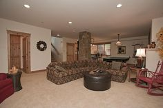 The family room, spacious enough for a pool table and a large sitting area by the fireplace.