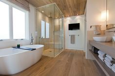 spacious bathroom with white bathtub, wooden towel's storage, bathroom basin with faucet, shower area with glass panels and lcd tv mounted o...