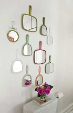 Vintage hand held mirrors as bathroom wall art