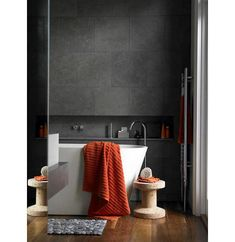 Love the dark grey tiles on the wall, white bath and the pop of the orange towels picking up the warm wood flooring. the pebble bath mat is fun too. Dark Bathrooms, Trendy Bathroom, Grey Slate Bathroom, Dark Gray Bathroom, Slate Bathroom, Bathrooms Remodel, Grey Bathrooms, Dark Grey Tile, Dark Grey Walls