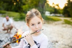 Little girl eating roasted marshmallow by a self-made campfire on.