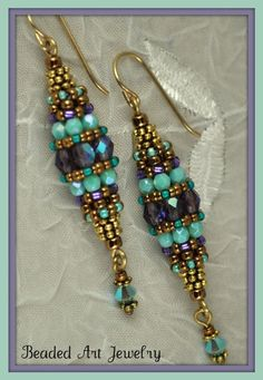 "Beaded Bead EarringsThese earrings are made using circular right angle weave to create a bead out of beads. They are made with Czech fire polish 4mm purple ab beads and 3mm Czech opaque turquiose luster, gold metallic Japanese seed beads, heishi and a Swarovski 4mm Turquoise ab crystal tassel on the end. They hang from a gold filled earring wire. They are 2 1/4"" long and are 1/2"" wide at the center"