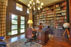 This traditional style home office is combined with a library. The cathedral ceilings allow for a massive built-in bookcase that reaches all the way to the ceiling. A rolling ladder is required to reach the top.  Ornate, rich hardwoods are abound in this space, in the desk, bookcase, and the floor.