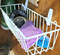 Command Hooks + Wire Basket = additional storage under the sink! Great for air drying sponges and scrubbers.
