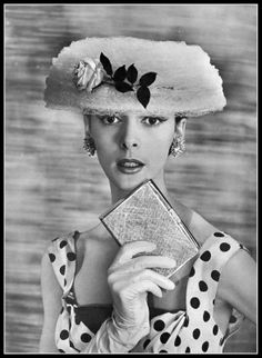 Kouka Denis in white lace hat with single pink rose by Legroux, polka-dot dress by Nina Ricci, gold minaudière and earclips by Sterlé, photo by Georges Saad, 1956