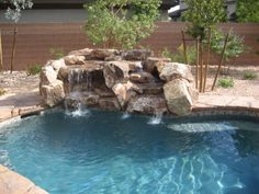 Bring Nature And Ambience To Your Backyard Pool Design By Adding A Rock Water Feature