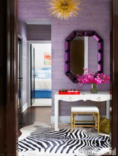 In the entry of a Manhattan apartment decorated by Lilly Bunn, a Romano mirror from Bungalow 5 picks up the purple in Phillip Jeffries's Juicy Jute grass cloth on the walls. Jacqui desk and Collette stool from Bungalow 5. Zanadoo hanging light by Arteriors. Faux-zebra rug from ABC Carpet & Home.