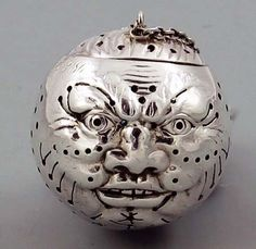 """Man in the Moon Tea Ball -  A rare antique sterling silver Gorham man in the moon tea ball with finely pierced detailed surface and a hinged lid. 1 1/2"""" across. Full Gorham marks on the bottom of the ball. Monogrammed and dated 1886."""
