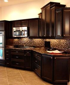 dark cabinets with lights above and below, red brink backsplash instead of tile and stainless steel appliances!!!