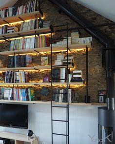 Bibliothèque de style industriel. Mise en avant du mur en pierre par un éclairage indirect. Architecte Yana.K