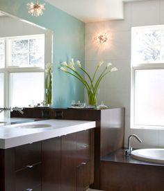 Serene #bathroom #design with dark #wood cabinetry, light blue wall, white countertops, and built-in #bathtub. So inviting!