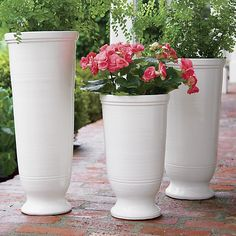 Potter-thrown terracotta planters are shaped into stately urns and glazed glossy cream to cache tall potted plants or dried botanicals.