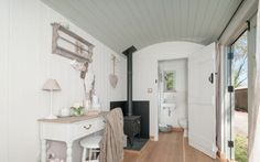 Beautiful interior of a luxury Shepherds Hut.  White shabby chic interior for a garden office or summer house with wood burning stove.  This garden office / summer house can be moved as it's built on a chassis!  www.blackdownshepherdhuts.co.uk